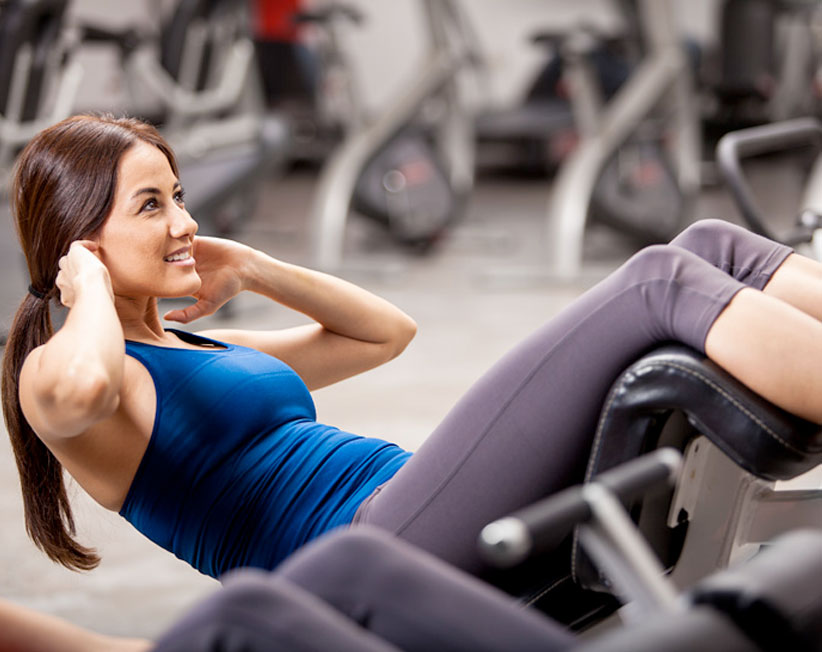 woman with brown hair in ponytail doing crunches at gym