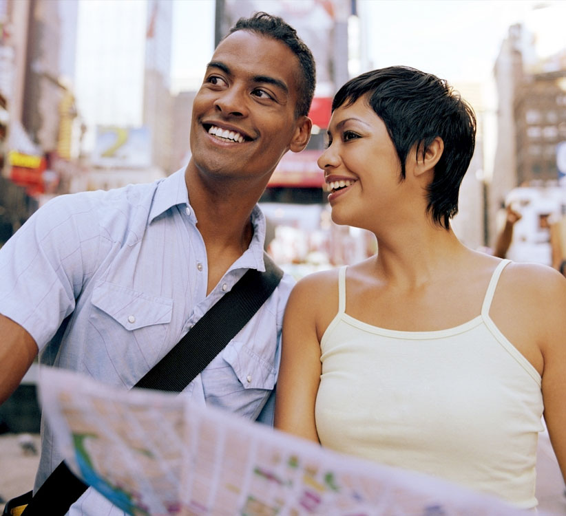 young couple smiling while looking at directions on map