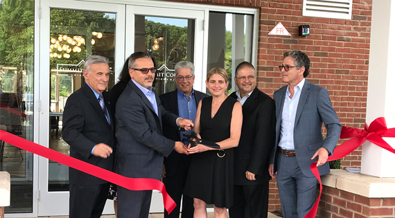 summit court team cutting ribbon to open apartments