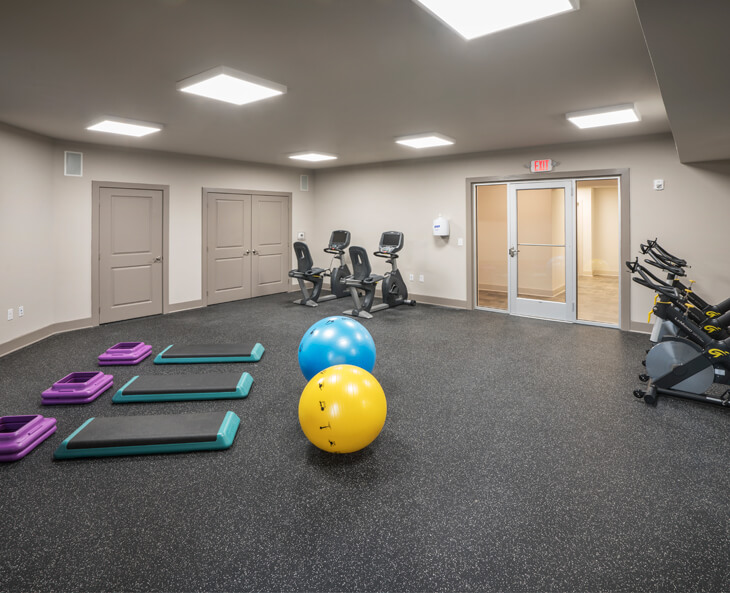 Apartment fitness center with exercise equipment and yoga balls