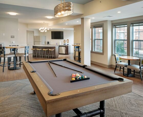 Apartment lounge area with pool table and sitting areas