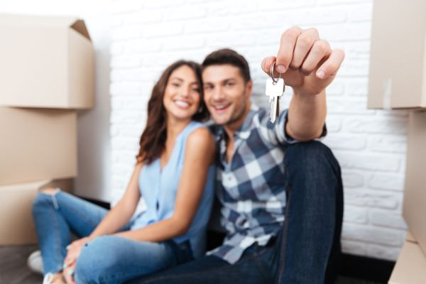 happy young couple holding out keys to their new apartment